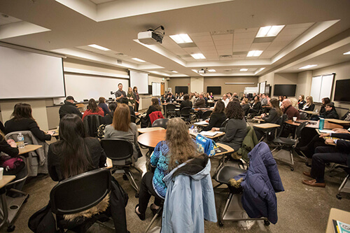 """Prospective student interviewees and their families listen intently to an interest table discussion on """"Life as a 1st Year Veterinary Student"""" with DVM Class of 2021 students Matt Schiffman, Brooke Matusiak, and Kayla Hoenert as part of the 2018 DVM Interview Day in Lynn Hall."""