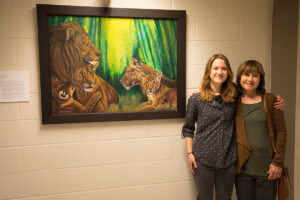 Kristen Thomas pictured with her mom beside painting