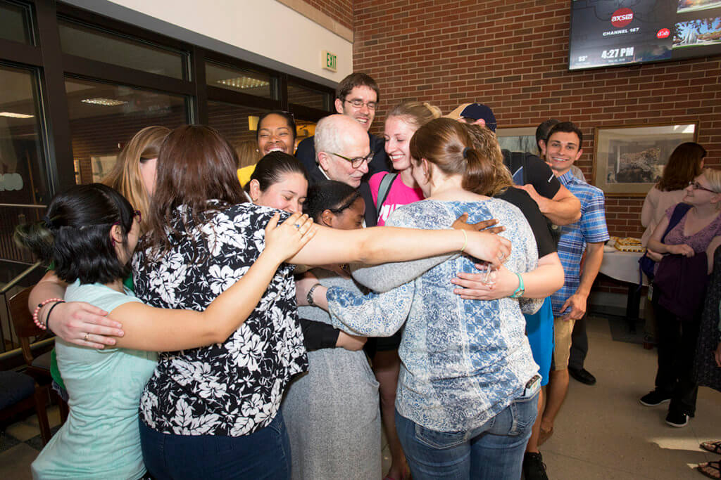Dr. Hullinger receives a group hug from students