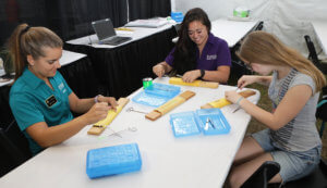 Veterinary students pictured with a fair goer practices suture techniques