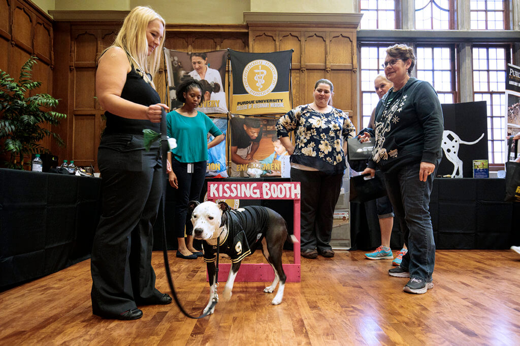 Lori Corriveau pictured with Carmella the dog and veterinary students at the Purdue Resource Fair