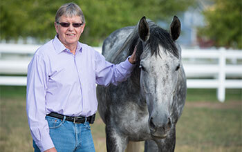 Dr. Wayne McIlwraith pictured with gray horse