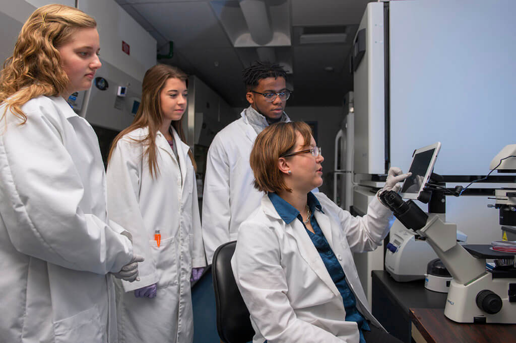 Dr. Marxa Figueiredo pictured with students in her lab