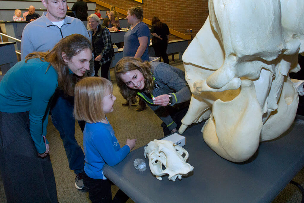 Brittany Rhodes pictured holding a tiny skull for an attendee to see