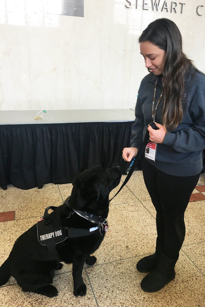 Frankie the dog receives a treat from Julianna in Stewart Center