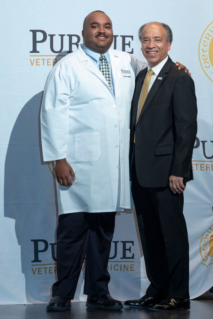 William Willis stands beside Dean Reed in front of photo backdrop for a picture on stage wearing his white coat