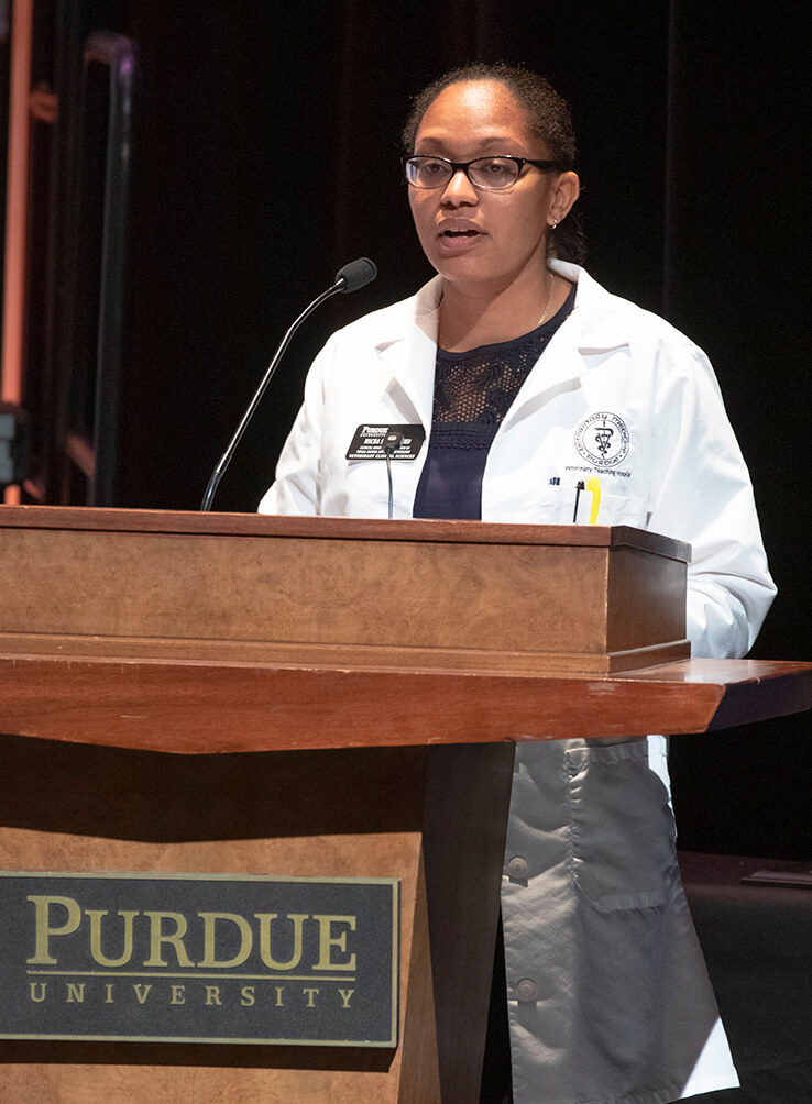 Dr. Micha Simons speaks on stage behind a podium