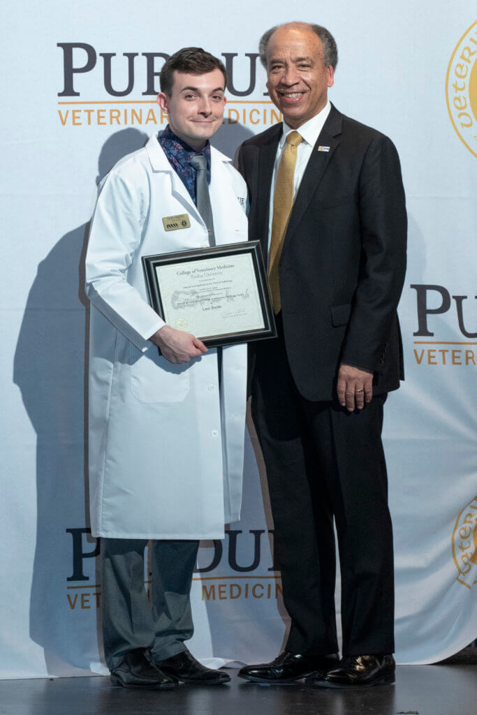 Levi Smith pauses for a photo on stage with Dean Reed holding his award certificate
