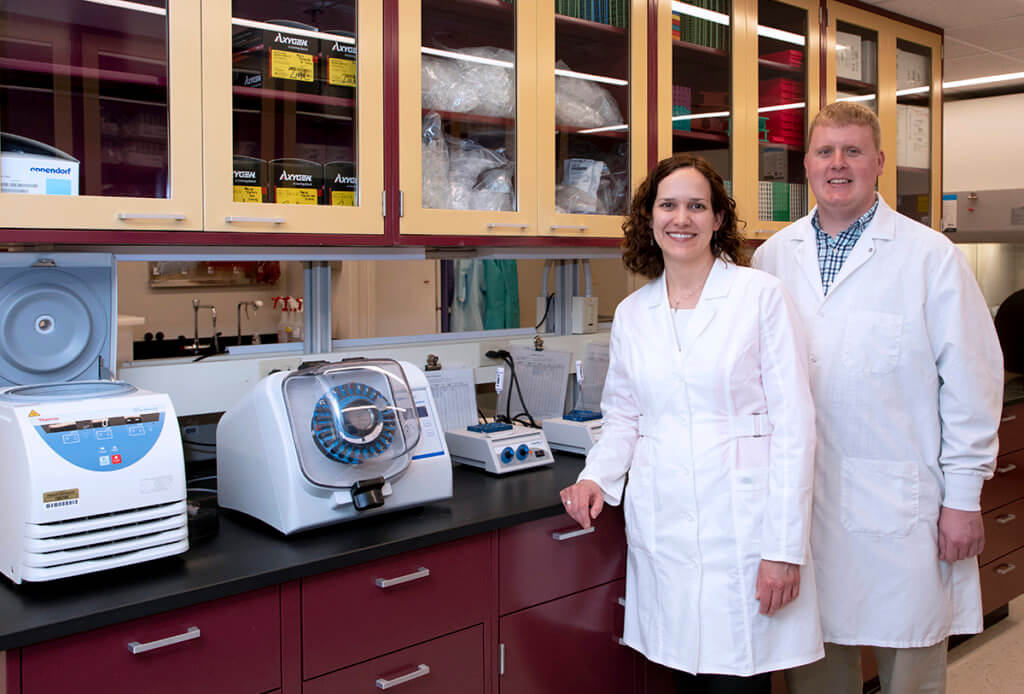 Dr. Hendrix stands in front of Dr. Bowen in front of a row of cabinets in a lab