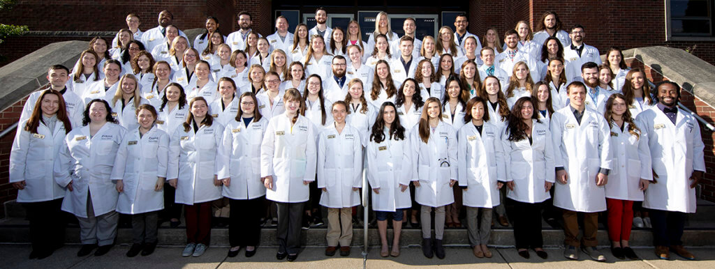 group photo of veterinary students on the steps of Lynn Hall wearing their new white coats