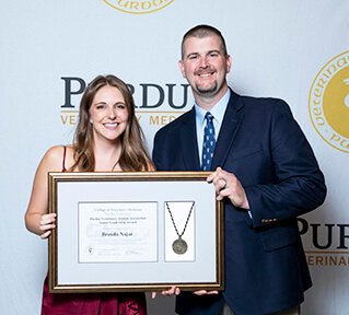 Brenda and John stand against a photo backdrop holding her award certificate and medal