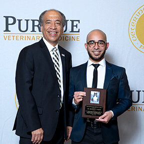 Dean Reed stands beside Dr. Pabon as he holds his award plaque