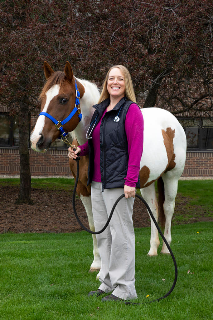 Sandy Taylor holds the harness of a painted horse outside