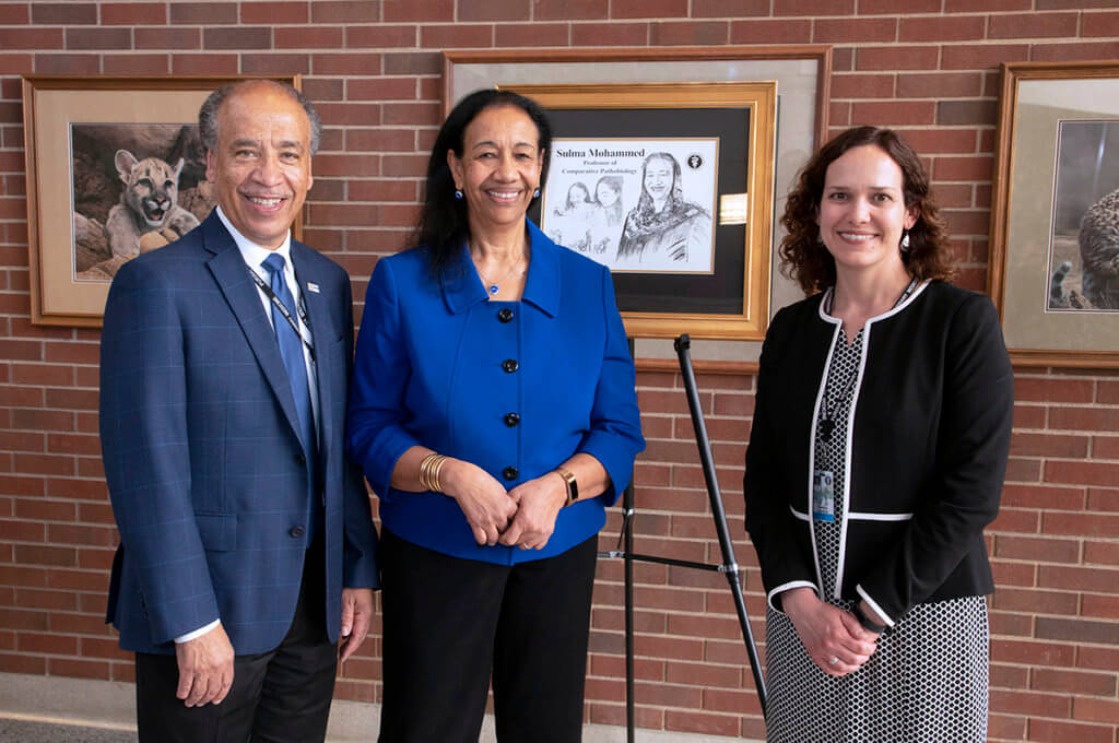 Dean Reed stands with Sulma Mohamed and Kenitra Hendrix with Sulma's illustration displayed in the background