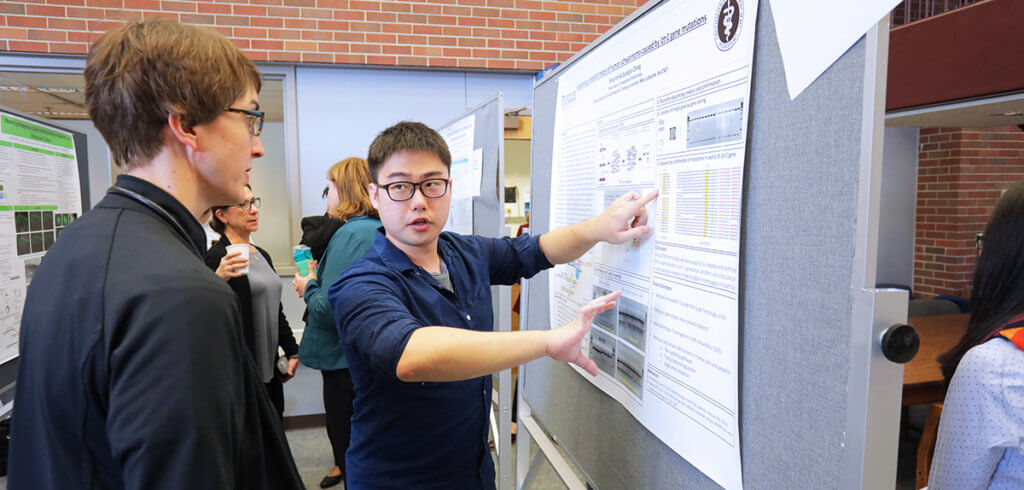 graduate student discusses research on his displayed poster with faculty member
