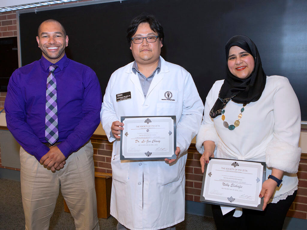 Research poster winners stand beside Dr. Thompson with their certificates