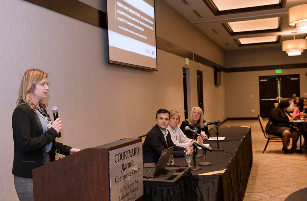 Industry experts sit as a panel in front of symposium attendees