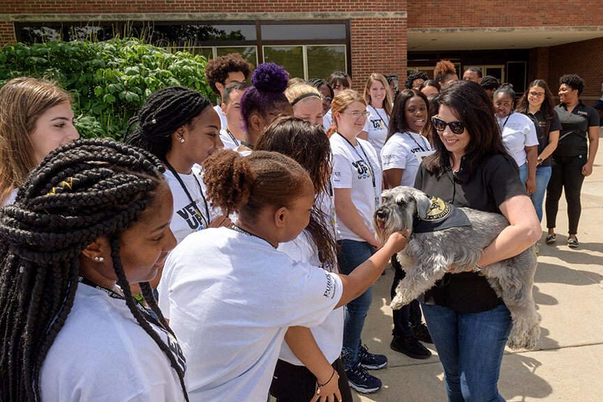 students greet Henry held by Janet Holcombas they meet outside Lynn Hall