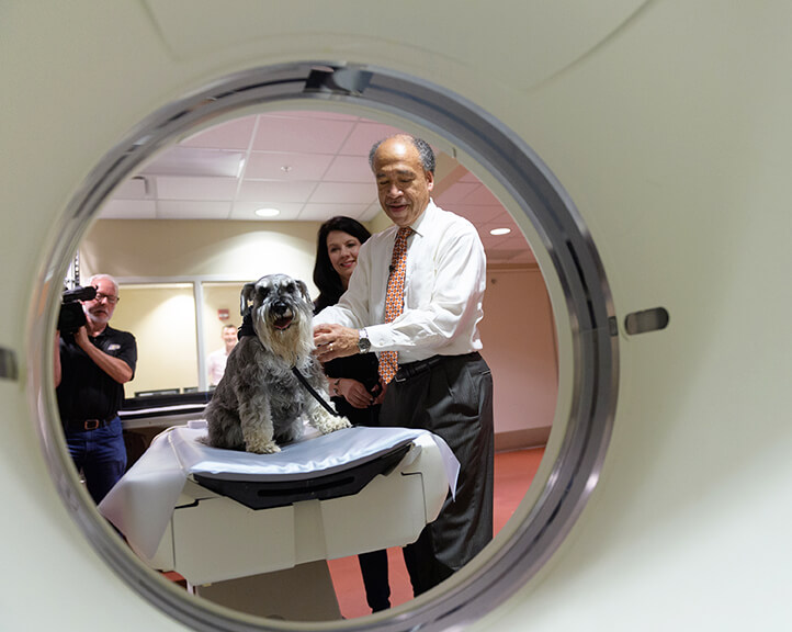 Henry looks into the CT unit with Dean Reed and Janet close by with the videographer in the background
