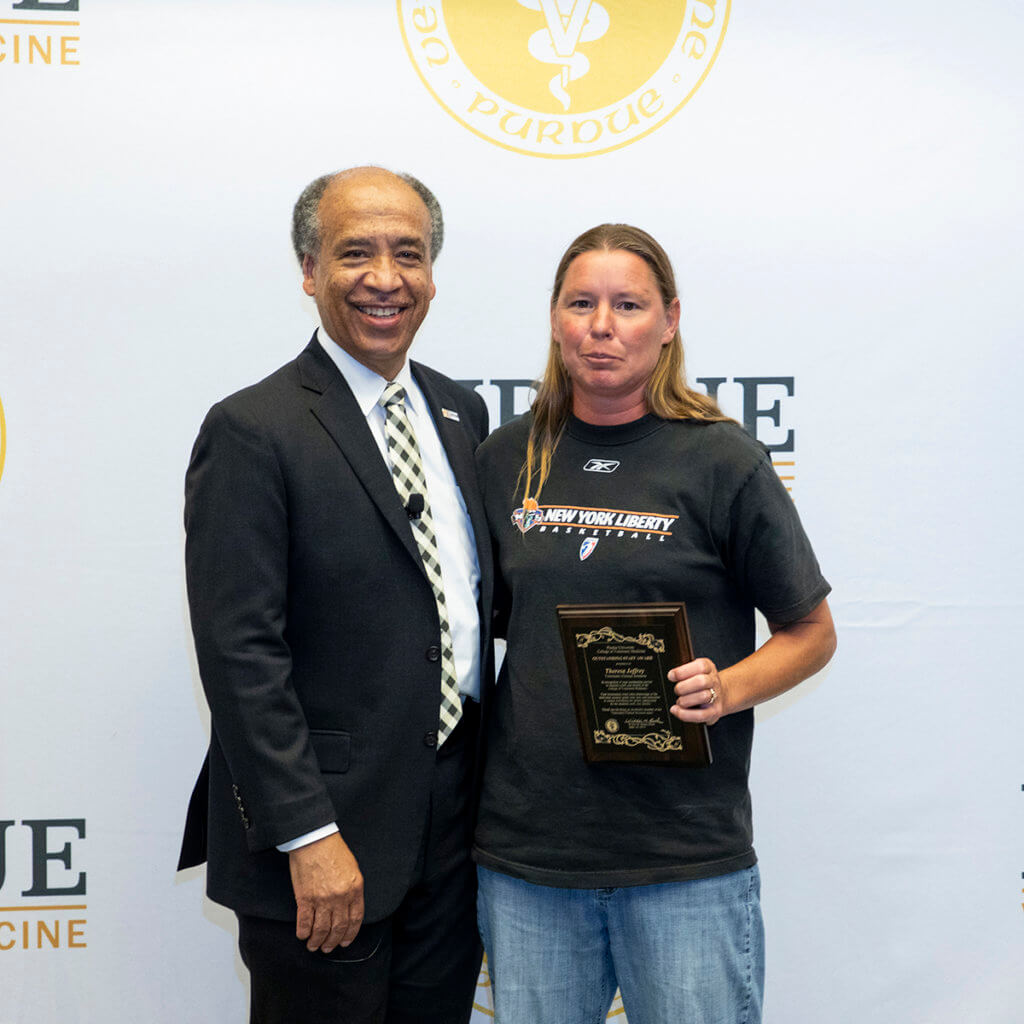 Theresa Jeffrey stands beside Dean Reed after receiving her award plaque