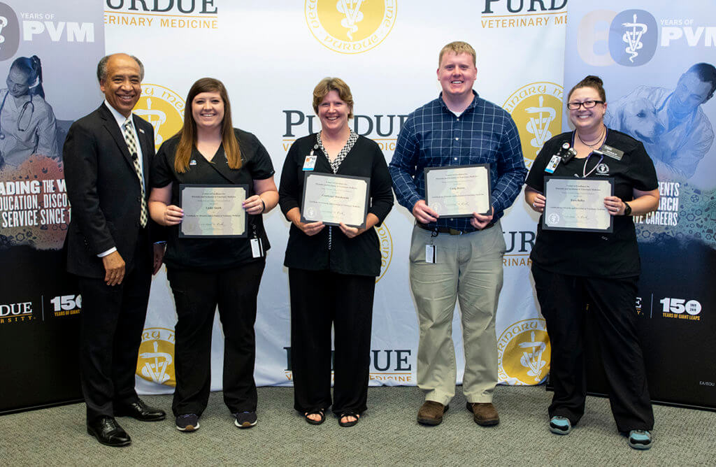 staff and faculty recognized for completing the online diversity certificate program stand with the dean holding their certificates of completion