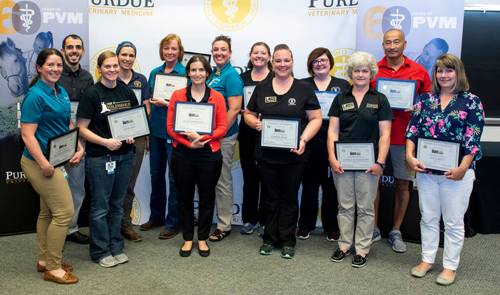 Bravo Awards recipients stand together holding their certificates with Dean Reed