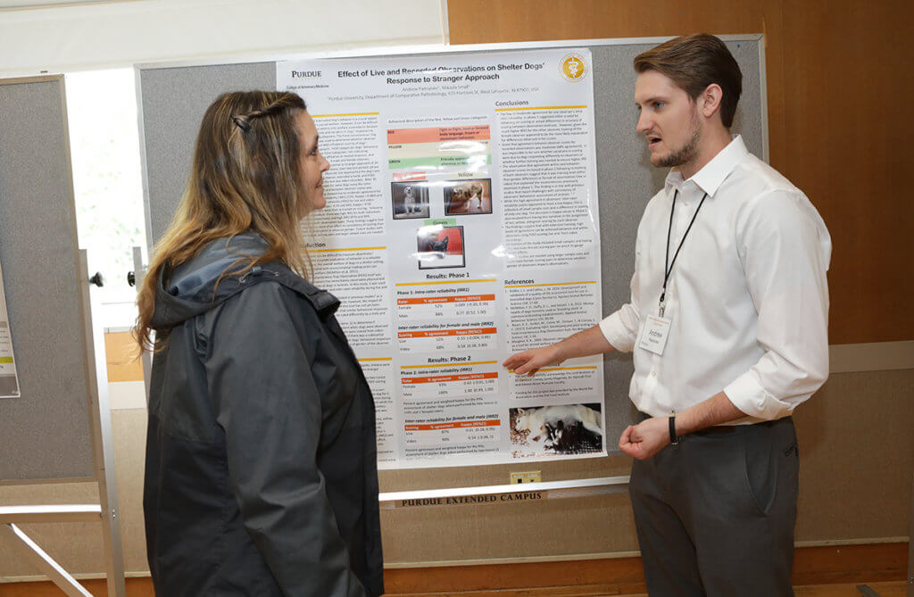 Andrew discusses his research with Angie as they stand in front of his research poster