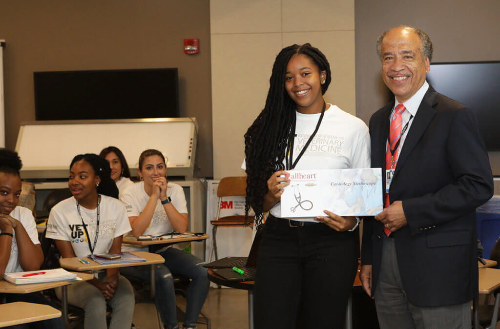 Candis holds up her new stethoscope next to Dean Reed as additional Vet Up! College participants look on