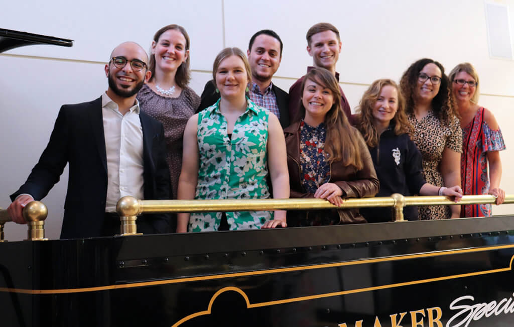 Outgoing interns stand together for a group photo aboard a replica of the Boilermaker Special train in DAUCH