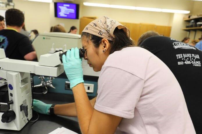 A camper looks into a microscope