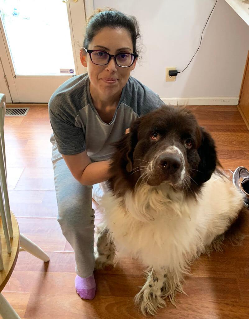 Vanessa kneels beside her dog, Titan, at home