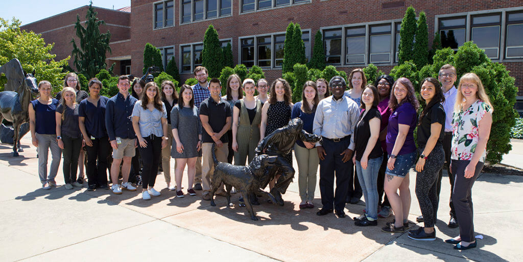 summer research program participants gather aound the Continuum sculpture in front of Lynn Hall