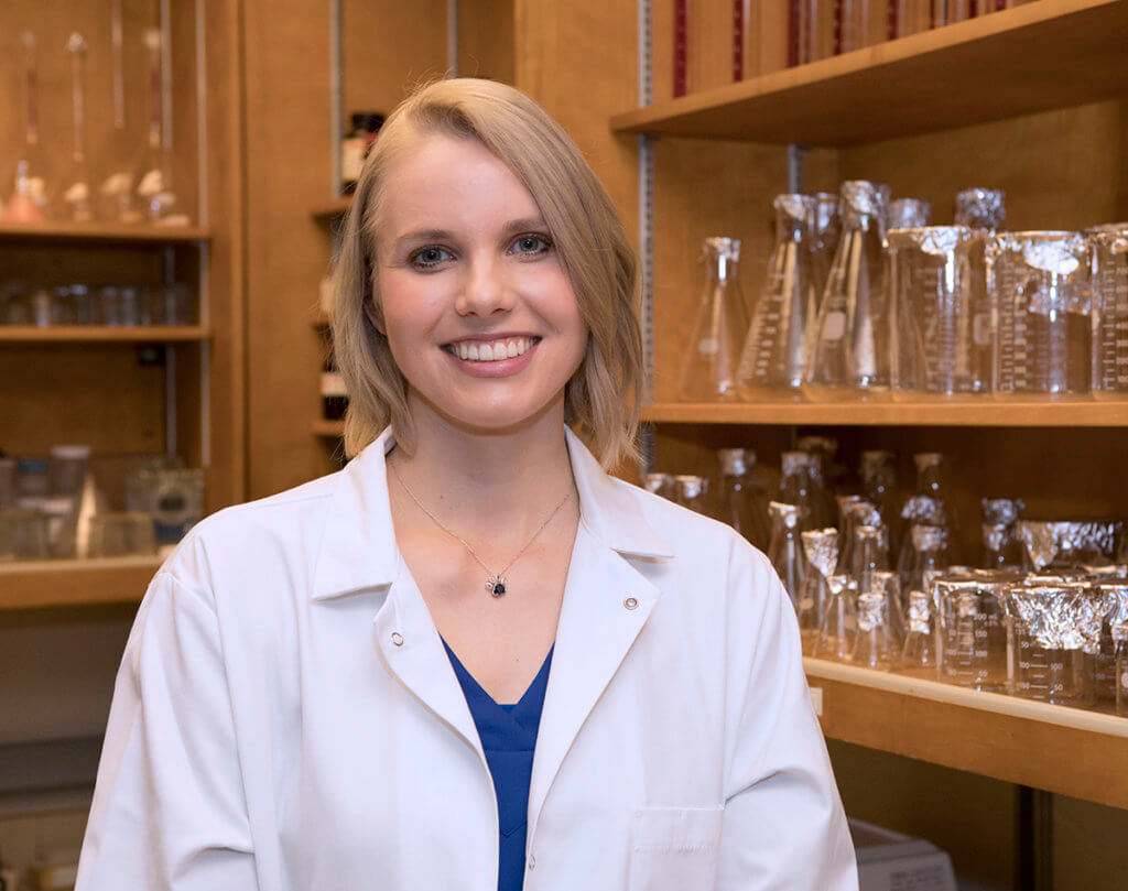 Alix stands in her laboratory wearing a white coat with shelves of beakers behind her