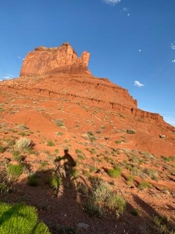 Sandy's shadow falls alongside a tall peak in the desert