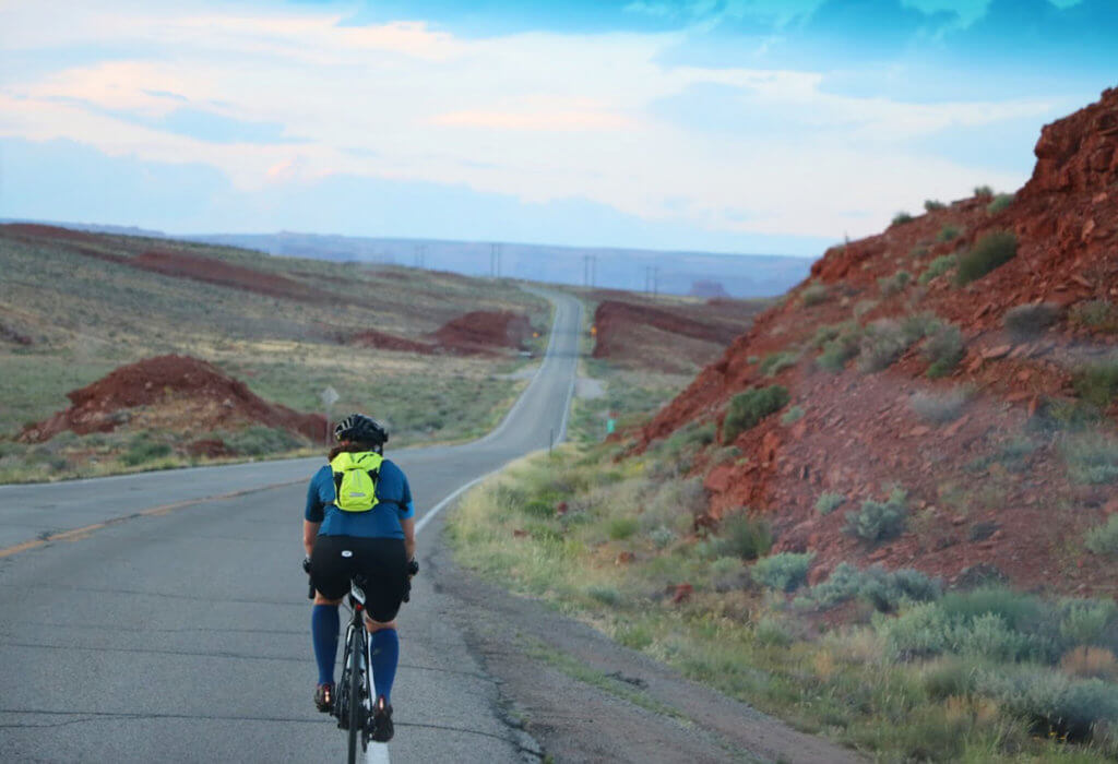 Molly rides her bike down a road with the vast Utah landscape around her
