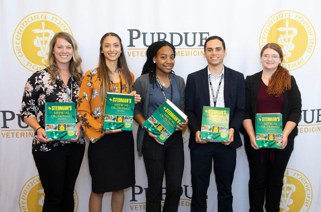 Outstanding Vet Up! College participants hold up their Stedman's Medical Dictionary books in front of the PVM logo banner