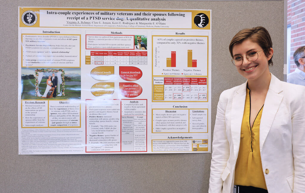 Viginia stands beside her displayed research poster