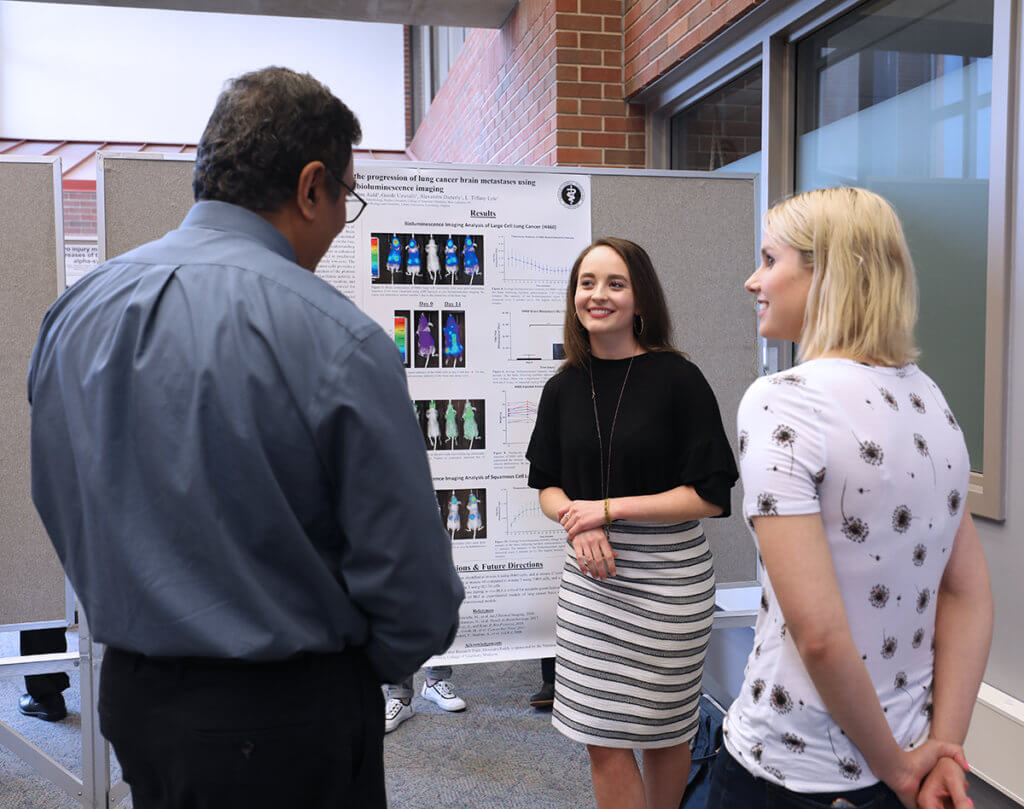 Alexandra stands in front of her research poster displayed in the library and speaks with Dr. Narayanan and her mentor, Alix Dieterly