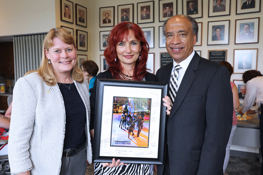 Dr. Nan holds a framed photo of the Continuum sculpture with Dr. Salisbury and Dean Reed by her side