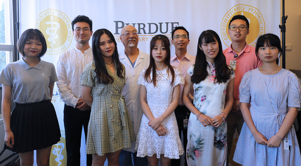 Sichuan Agricultural University students and a faculty member join Dr. Ko for a group picture in front of the PVM logo banner