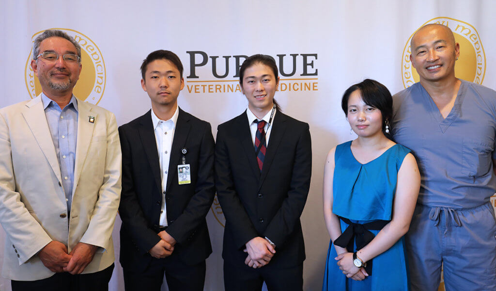 Rakuno Gakuen faculty and students are joined by Dr. Inoue for a group photo in front of the PVM logo banner