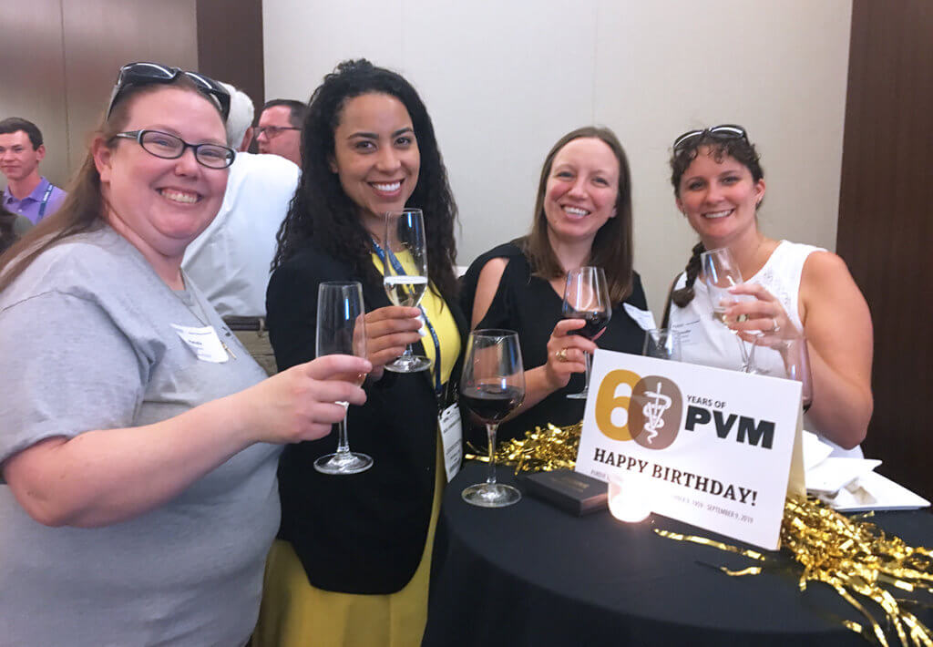 PVM alumni hold up their glasses for a toast at the AVMA alumni reception