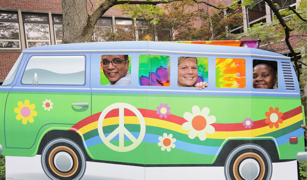 Dr. Narayan, Julie, and Tempess stand behind a 60s van photo prop at the appreciation event