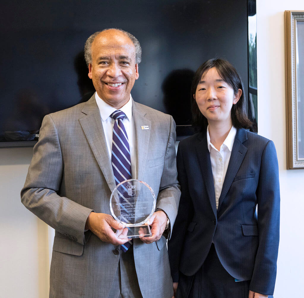 Dean Reed stands beside Dr. Yamamoto-Samejim holding a commemorative plaque