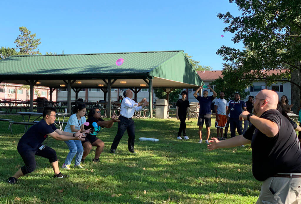 Kitasato students and veterinary medicine faculty and staff play water balloon toss outside in a park