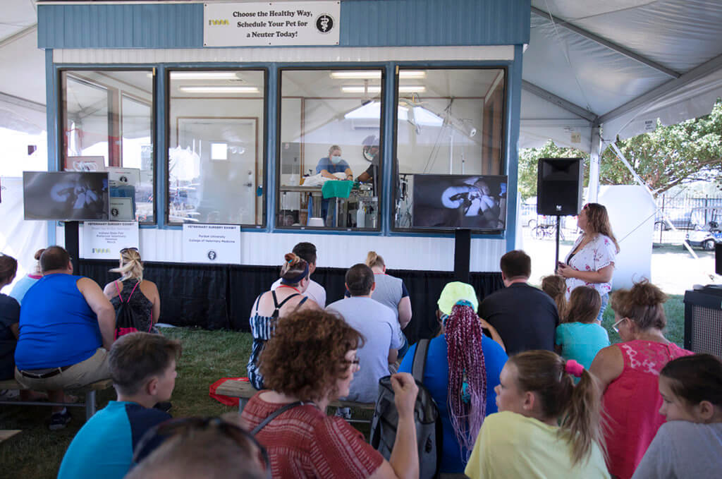 An audience of state fair attendees sit under a tent to watch a live dentistry procedure in a sterile surgery suite in front of them