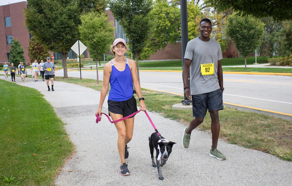 Dog Jog participants walk and run along a path on Purdue's campus