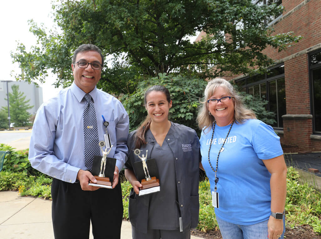 Dr. Narayanan and Christa hold up their corhnole tournament trophies joined by Andi outside Lynn Hall