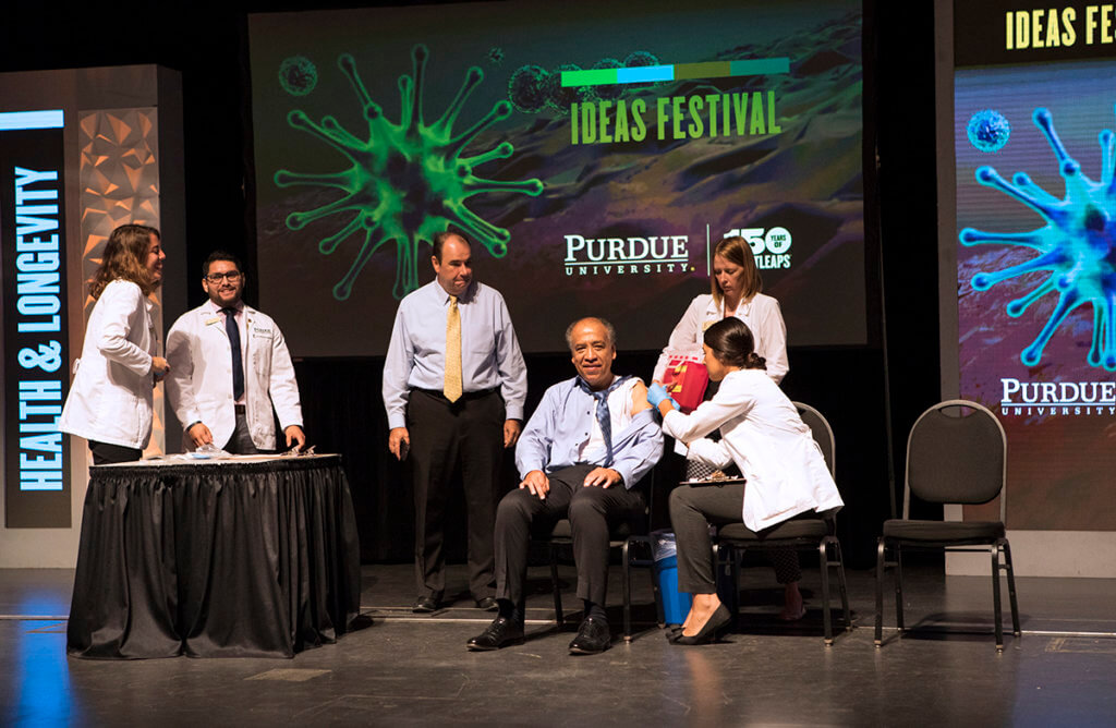 Dean Reed receives a flu shot in his arm while seated on stage