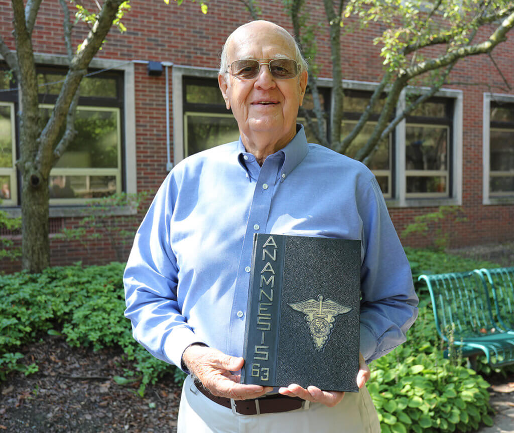 PVM alum Gary Pearl stands in the courtyard holding his class yearbook from 1963